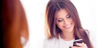 девушка смотрит в телефон и улыбается