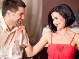 мужчина и женщина смеются за ужином