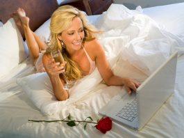 девушка лежит на кровати с ноутбуком