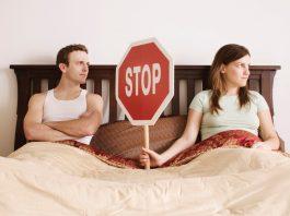 женщина держит знак стоп в постели с мужчиной