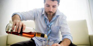 мужчина наливает себе алкоголь